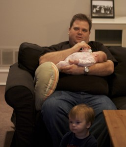 Brenden watches tv while Patrick feeds Emily.