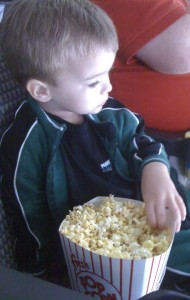 Kicking back with his popcorn snack and a little hockey.